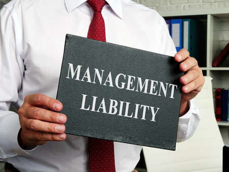 A man holding a sign with the inscription management liability.