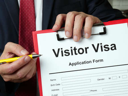 Visitor visa application form. The lawyer offers papers.