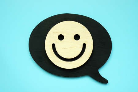 Positive customer feedback or review concept. Wooden Smiley face.