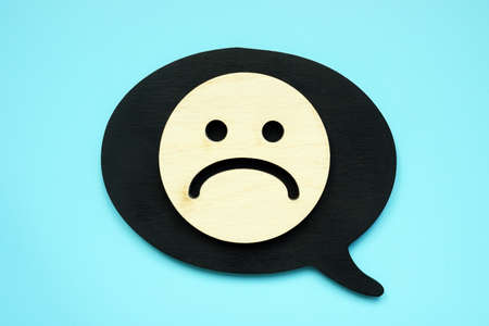 Small Sad face as symbol of negative feedback or review.