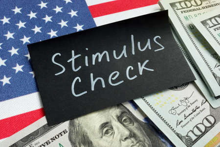 Stimulus check words, money and USA flag.