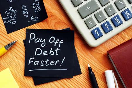 Pay off debt faster handwritten memo and calculator.