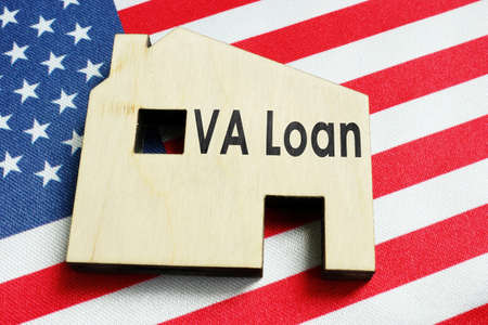 VA loan sign on the wooden home and American flag. Reklamní fotografie
