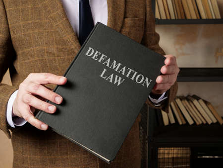 Lawyer in suit holds Defamation law book.