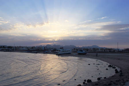 Bay and abandoned beach. Broken old boat on the shore. Sun rays peek out from behind the clouds. Low mountains in the distance. Resort on the Red sea coast, Safaga, Egypt