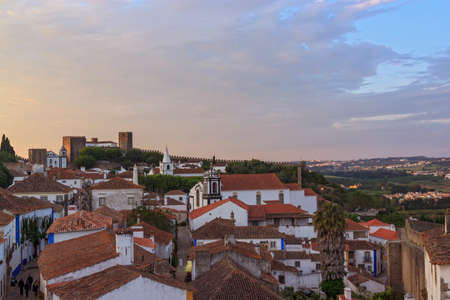 View of narrow streets and castle of Obidos from wall of fortress. Scenic old town with medieval architecture in the sunset. White houses red tiled roofs. Popular touristic destination.