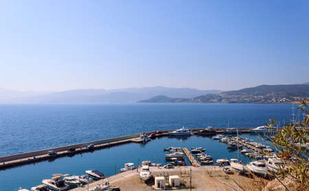 Marine pier with yachts and speedboats. Mountains on the other side of the bay. Travel photography. Stock fotó