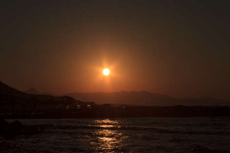 Sunset over the sea and the mountains in Kokkini Hani, Crete, Greece. Scenic seaside landscape in the evening. Banco de Imagens