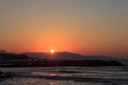 Sunset over the sea in Kokkini Hani, Crete, Greece. The sun disappears behind the mountain. Scenic seaside landscape in the evening.