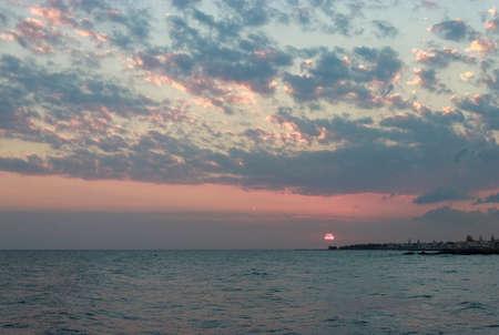 Sunrise over the sea in Kokkini Hani, Crete, Greece. Scenic seaside landscape in the cloudy morning.
