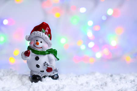 Snowman in the snow with bokeh blurred light. Stock Photo