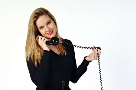 Smiling young woman speaking on a telephone, with the cord twisted around her fingers. Stock Photo - 661444