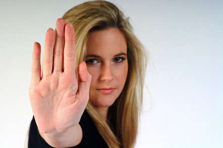 outwards: Young woman making a stop gesture, palm outwards. Stock Photo