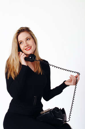 A young woman talking on an old fashion black telephone. Stock Photo - 661442