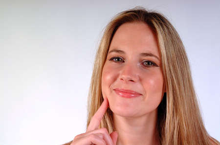 Young blonde woman, smiling with fore finger on her chin. Shot on a white background with space left on the left for text etc. photo