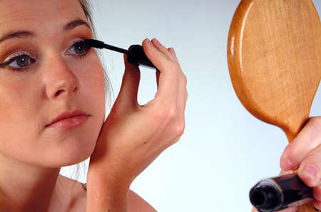 Young woman gazing into a hand mirror whilst applying her mascara. Shot against a white background. photo