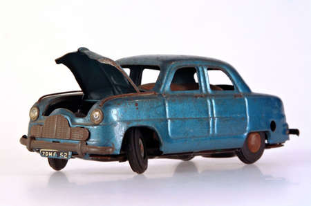abandoned car: A battered and broken tin toy car, with bonnet open. Stock Photo