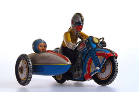 sidecar: Retro clockwork tin toy, man riding motorcycle with child in the sidecar.