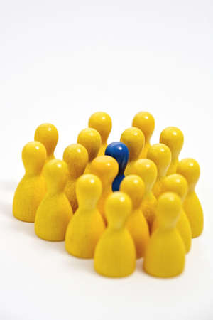 incorporated: One blue counter in a group of yellow counters, illustrating inclusion and acceptance. Narrow depth of field, isolated on a white background.