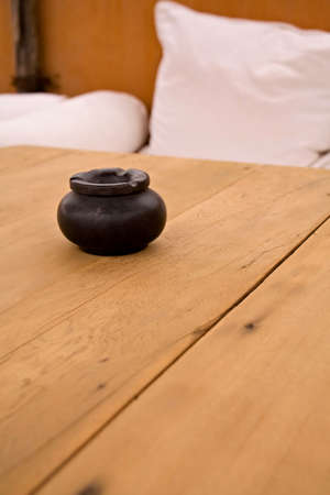 An earthenware ashtray sitting on a wooden table, with white cushions in the background. photo