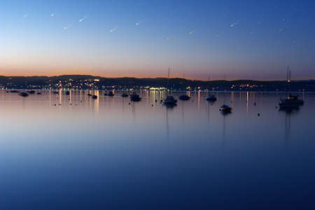 City coast line behind boats with a sky of shooting stars, during a twilight sunset, at a long exposure time