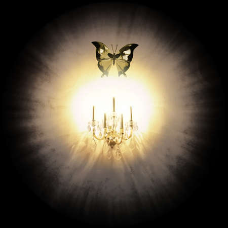 radiant light: A crystal moth is attracted by a glowing crystal candle light holder on a wall, isolated on black.                                         Stock Photo