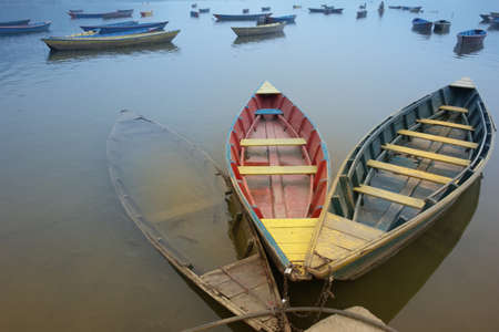 Three old boats, bound together, with weathered, contrary color on them. The colorless one is sunken, and has swimming fishes in it.                                 Stock Photo