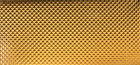 gradual: tri�ngulos de oro en una textura de cuero en los cambios graduales de luz con diminutos trazos ondulados Foto de archivo