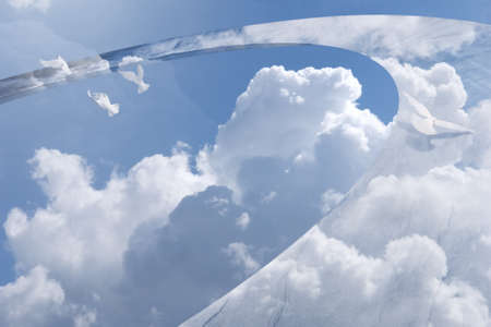 abstract, round sky sculpture with a cloud reflection on it and flying, white doves break free of the circle Stock Photo
