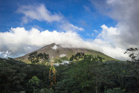arenal volcano of costa rica, with clouds making shadows and bright green vegetation, where at the bottom of the mountain and a shamanic tree creature, walking through