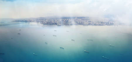 panama city aerial view with sun rays shining on bright water spots and a ship fleet on the way to the panama canal