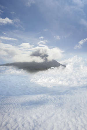presage: aerial view from above the clouds to a volcano island with circle cloud signs over it, to warn that a erruption may come soon