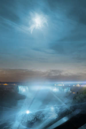 illuminated niagara waterfalls night view, from the canadian side, with a wet moon effect and light rays in the foreground in long exposure