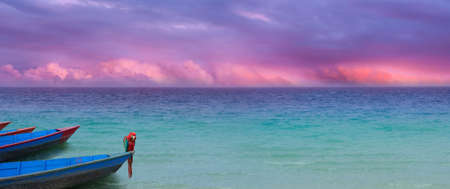 exotic ocean panorama with a colorful cloudscape and boats with a parrot in similar, harmonic colors