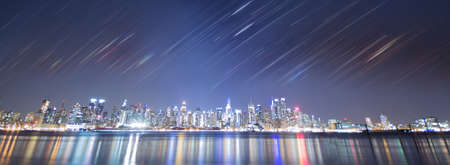 new york city night coastline panorma, with motion blured rainbow stripes, layered from moving diamond lights