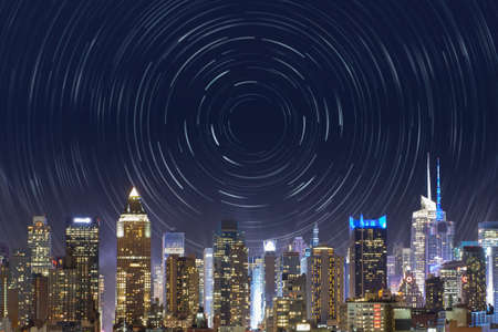 new york city, midtown manhattan, view from the outside to the bright time square, with a star trails effect in the night sky, for a time concept, bound to this famous place