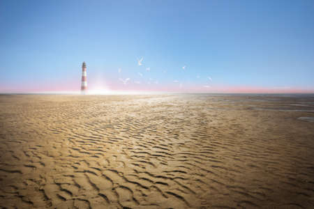 lighthouse on a dried ocean, low tide coast, with sea gulls over the sunset and tracks of waves in the sand Stock Photo