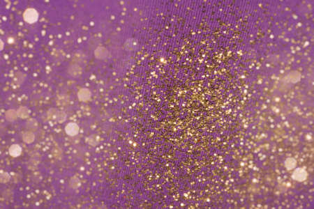 glistening: golden glitter background on a purple fabric structure, fading into layered bokeh particles