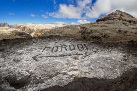 Pordoi mountains plateau in the Dolomites, with a written marker on a stone and the Piz Boe peak Stock Photo