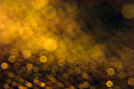 Golden heptagon bokeh background, fading into black