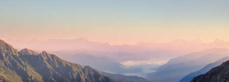 Mountain valley in different color grades and tones, caused by morning haze, viewed from the top of the Edelweissspitze