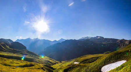 Morning sunrays over a long, hazy valley, viewed from High Tauern and snow remains in the mids of summer Stock Photo