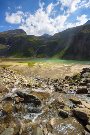 Standing in the center of a wild mountain creek, flowing in rivulets into the Nassfeldspeicher Lake, a so called power place, with sun rays enlightening the water surface, in the High Tauern National Park, Austria