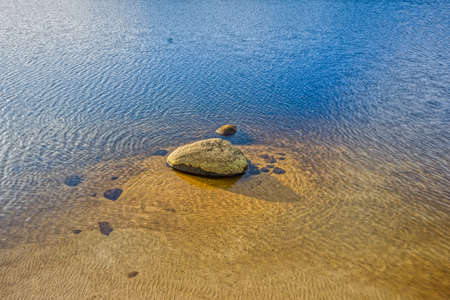Stone in a lake in the sand with several ripple textures