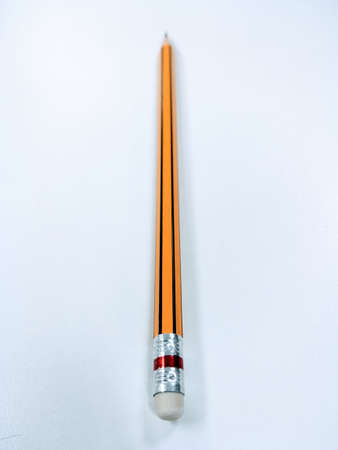 An orange pencil placed on a white background.