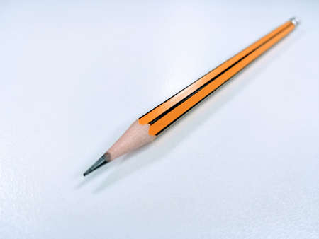 A beautiful orange pencil placed on a white background.