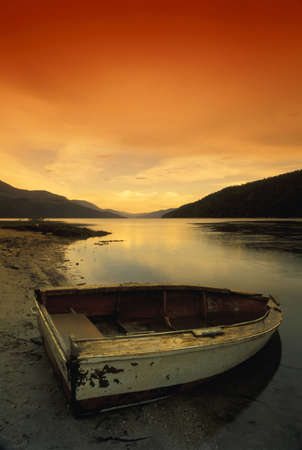 rowboat: Rowboat and lake at sunset with mountains in the background