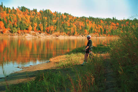 Cyclist taking a break by river in autumn Stock Photo
