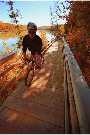 Cyclist on wooden pathway by river Stock Photo - 6212916