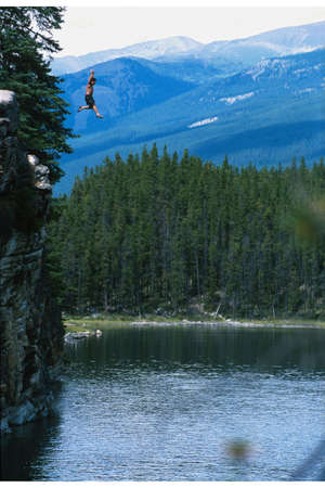 Man jumping off cliff into lake photo